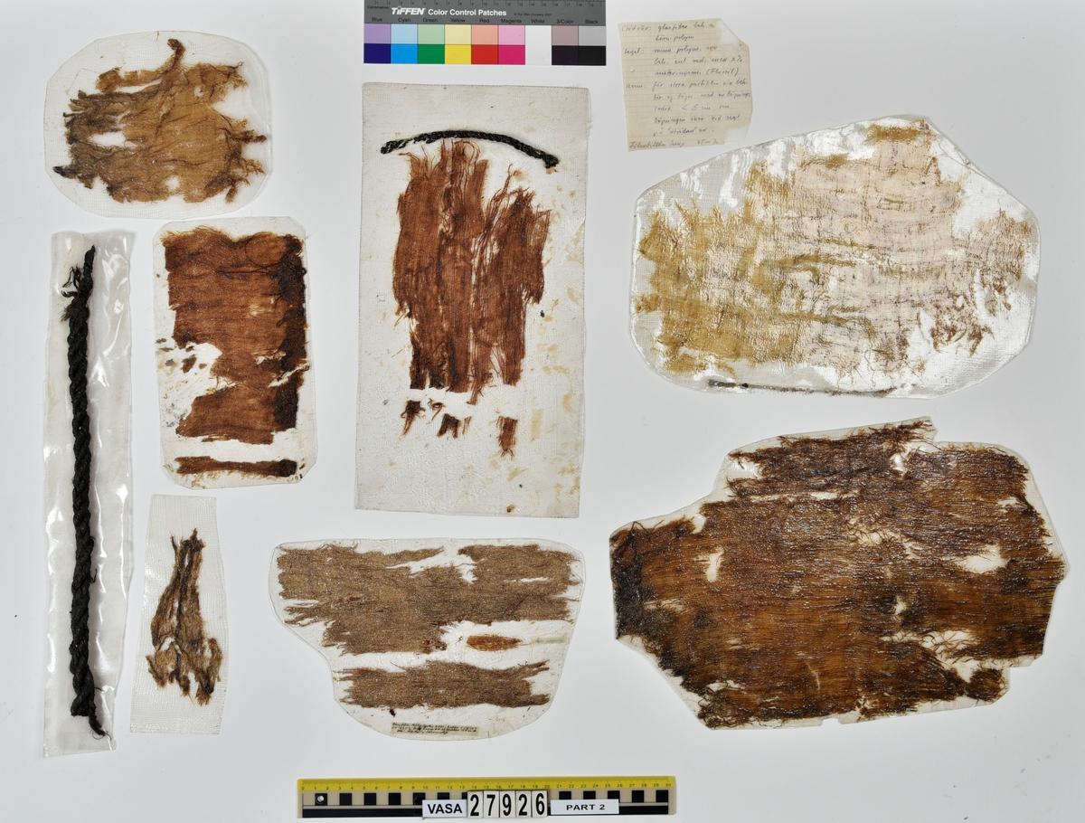 Många olika textilprover av olika segel och kläder som tagits som provbitar för olika sorters konserveringsprov samt för analyser av fibrer m.m.