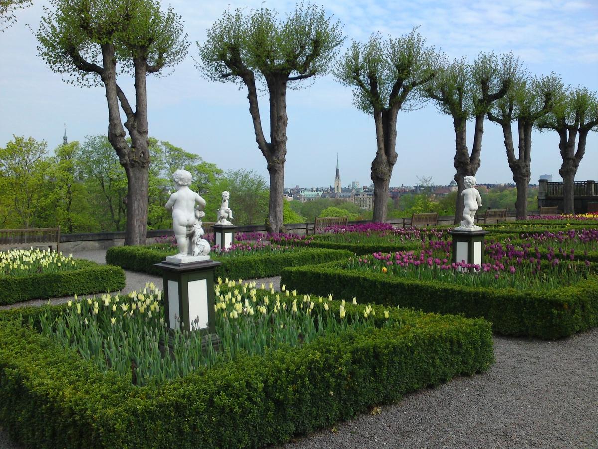 I förgrunden blommar tulpaner i olika färger övervakade av några figurer. Träd i rad rammar in Östermalm i bakgrunden.