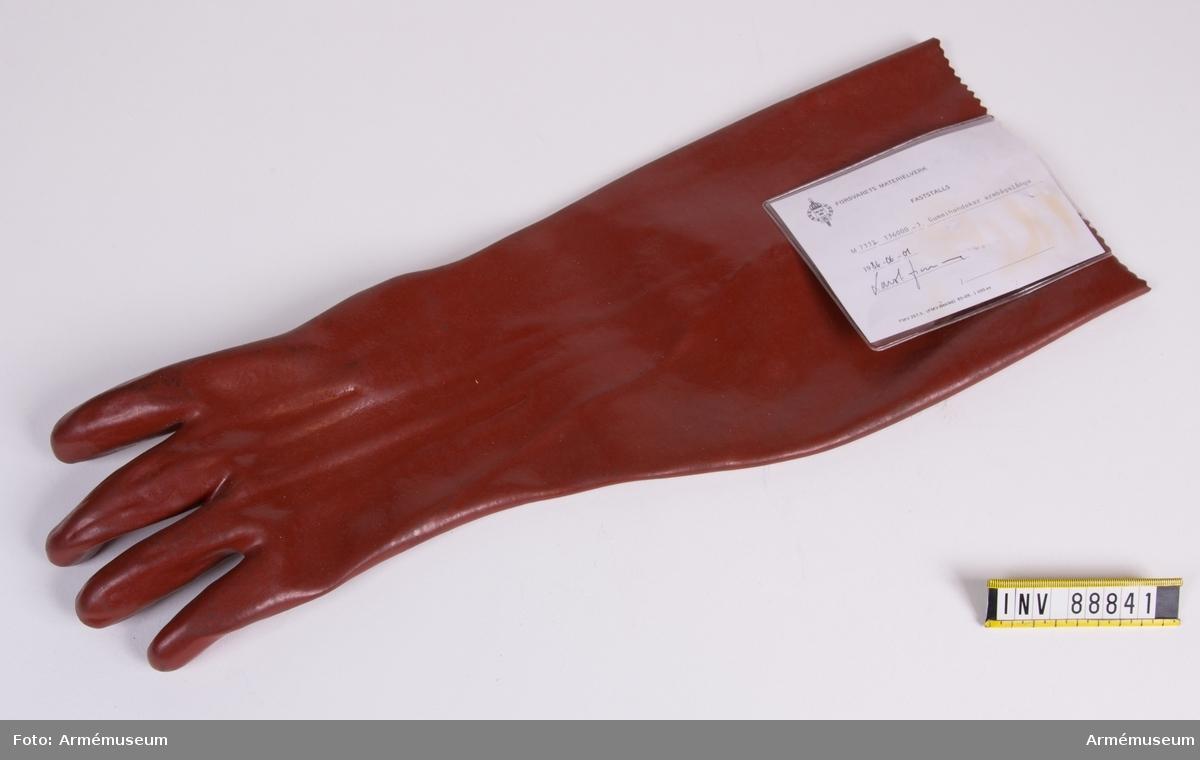 """Armbågslång handske i röd plast för vänster hand.  På ena sidan står i grön text: """"NORTH HYGESAN STANDARDWEIGHT  COTTON AND P.V.C. 9 1/2"""". Vidhängande modellapp med text: """"Försvarets materielverk. Fastställs. M 7332-136000-3. Gummihandskar armbågslånga. 1986-06-01. (oläslig underskrift)."""""""