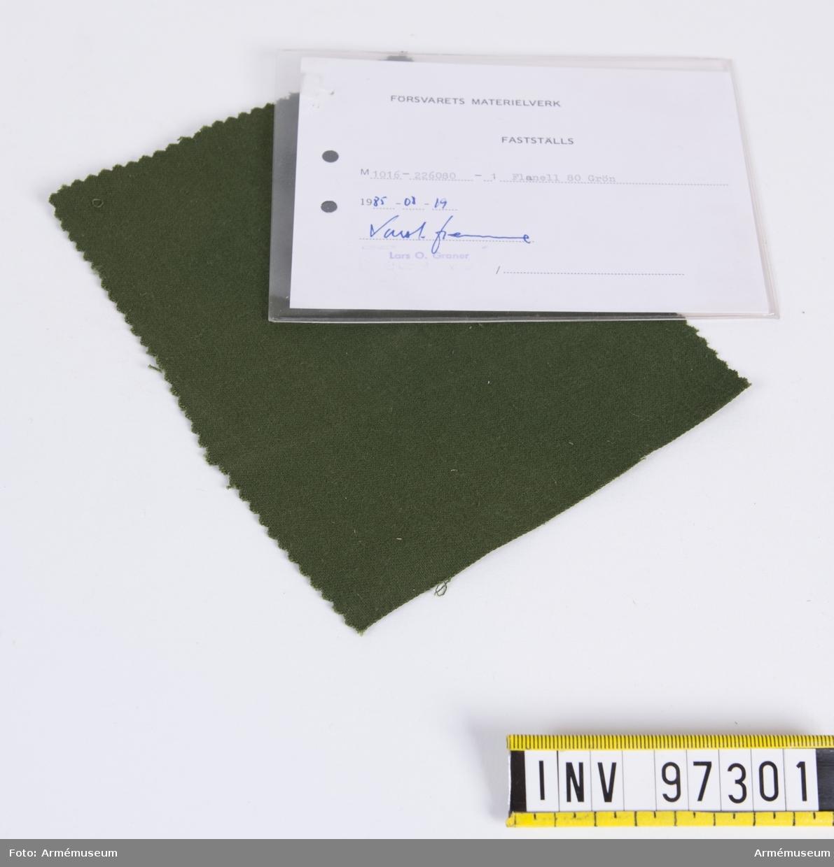 """Vidhängande modellapp med text: """"Försvarets materielverk. Fastställs. M 1016-226080-1. Flanell 80, Grön. 1985-08-20.  (oläslig sign)"""""""