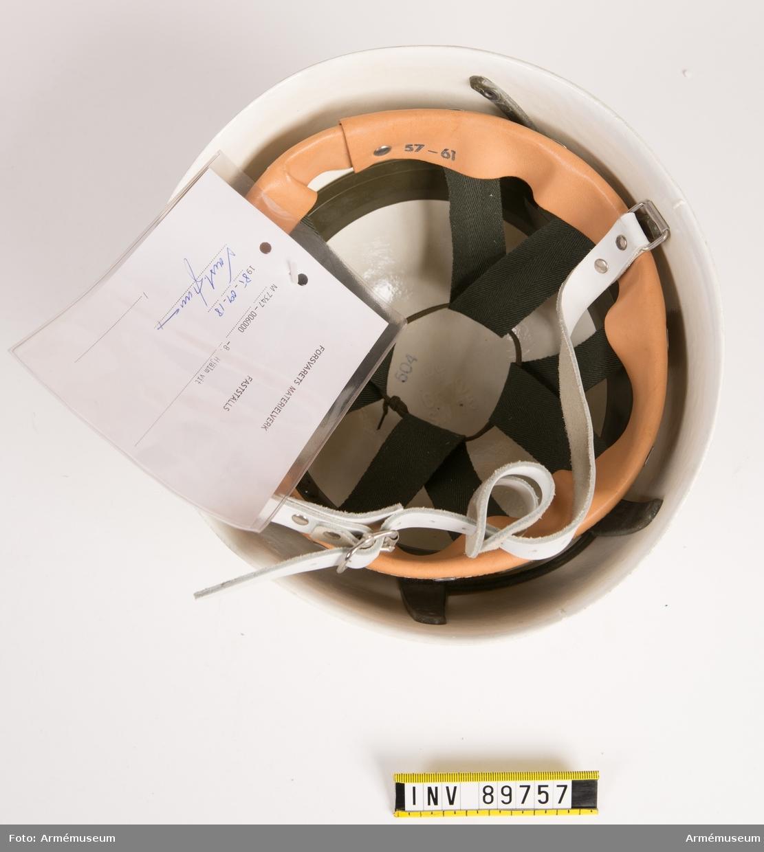 """Vitmålad metallhjälm. Inredningen av plast, tygremmar och svettrem av läder. Vit hakrem. Storlek 57-61 stämplat på svettremmen. Vidhängande etikett med text: """"Försvarets materielverk. Fastställs. M 7347-006000-8. Hjälm, vit. 1985-09-18 (oläslig signatur)"""""""