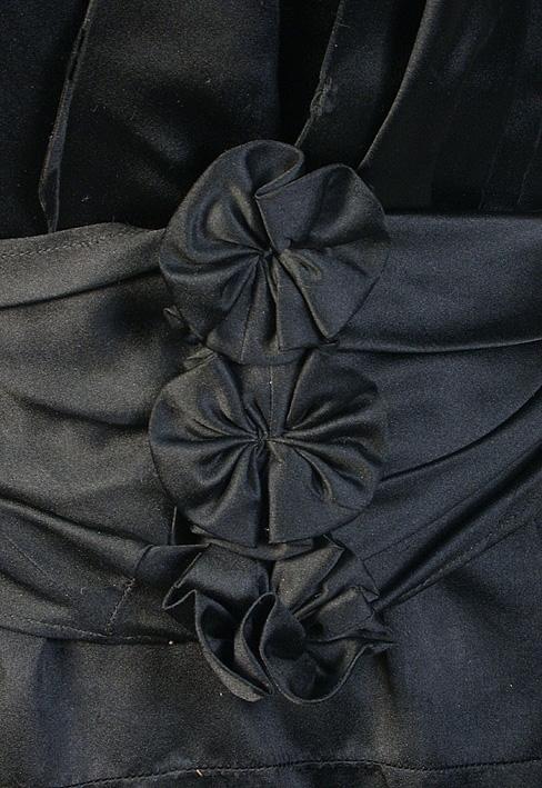 Bestående av kjol, liv och skärp av svart siden.  Stadkanterna röda på sidenet. Figurskuret liv med insydda fjädrar. Hopfästes framtill med hyskor och hakar, lagda veck ovanpå livet i snibb fram. Rak upprättstående krage kantad med svart uddspets. Livet fodrat med vinröd o svartrandigt bomullstyg. Figurskuret ryggstycke med snibb neråt. Ärmen lång, figurskuren, veck över axeln, slag vid ärmlinningen. Ärmarna fodrade med kyprad lärft. Svarta snörmakerier över axelprtiet går ner både fram och bak på ryggen. Randigt foder i bommullssatin. På höger del av innerfodret en påsydd ficka. Kjolen slät framtill. Lagda veck baktill kring sprundet. Kilskuren i 7 (ej hela) våder. Kjolen fodrad med svart vaxad tuskaft bomull.   Skärp i samma material som kläningen. Insydda fjädrar. Garnering framtill av tyget, 3 st roseliknande blommor i samma tyg. Skärpet rynkat mot kortändarna. Knäppt med hyskor och hakar. Mått: Liv 46 cm, kraghöjd 5 cm, ärmlängd 42 cm, axel 9 cm.