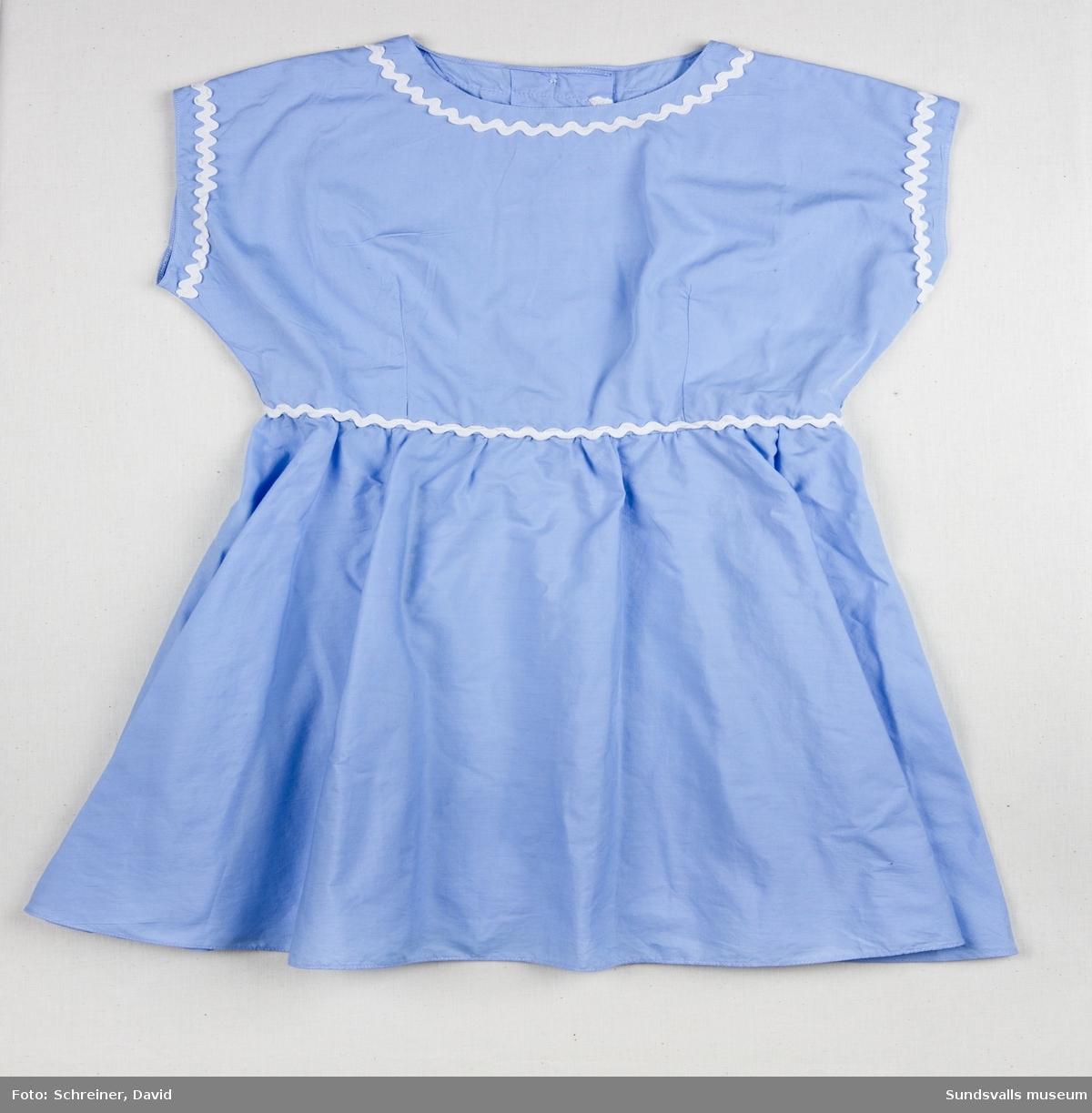 En ljusblå ärmlös klänning med utsmyckning runt ärmhål, halsrundning och midja med vitt dekorband.