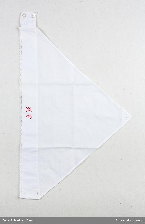 Ett vitt huckle med knäppning i nacken. Hucklets har utsmyckats med en virkad spetskant samt broderats med initialerna K F - Karin Fredriksson.