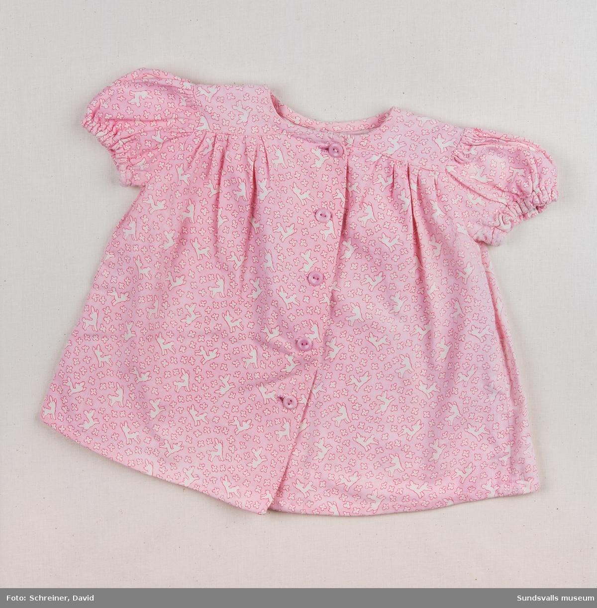 En rosa flickklänning i  småmönstrad bomull.  Klänningen är  är skuren strax nedanför axeln och knäpps framtill med fem stycken rosa plastknappar.