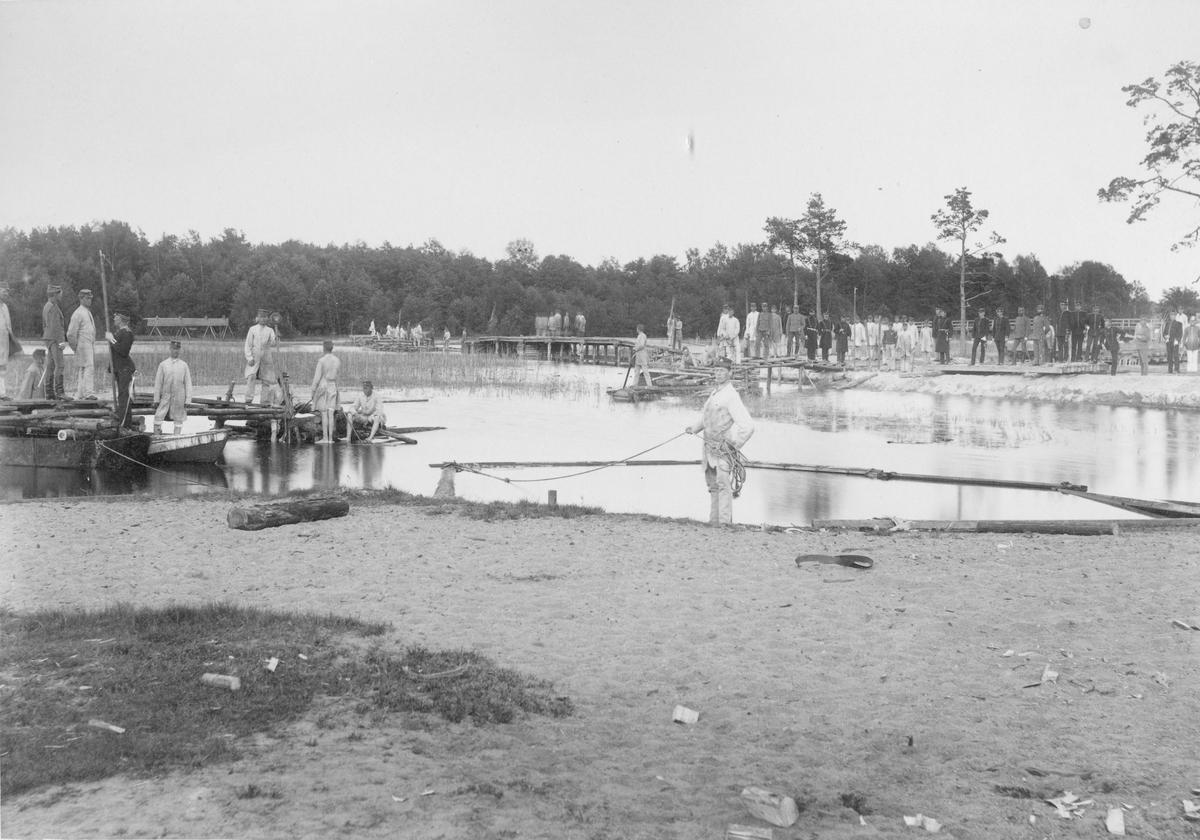 Soldater och officerare från Karlsborgs fästning vid vattendrag.