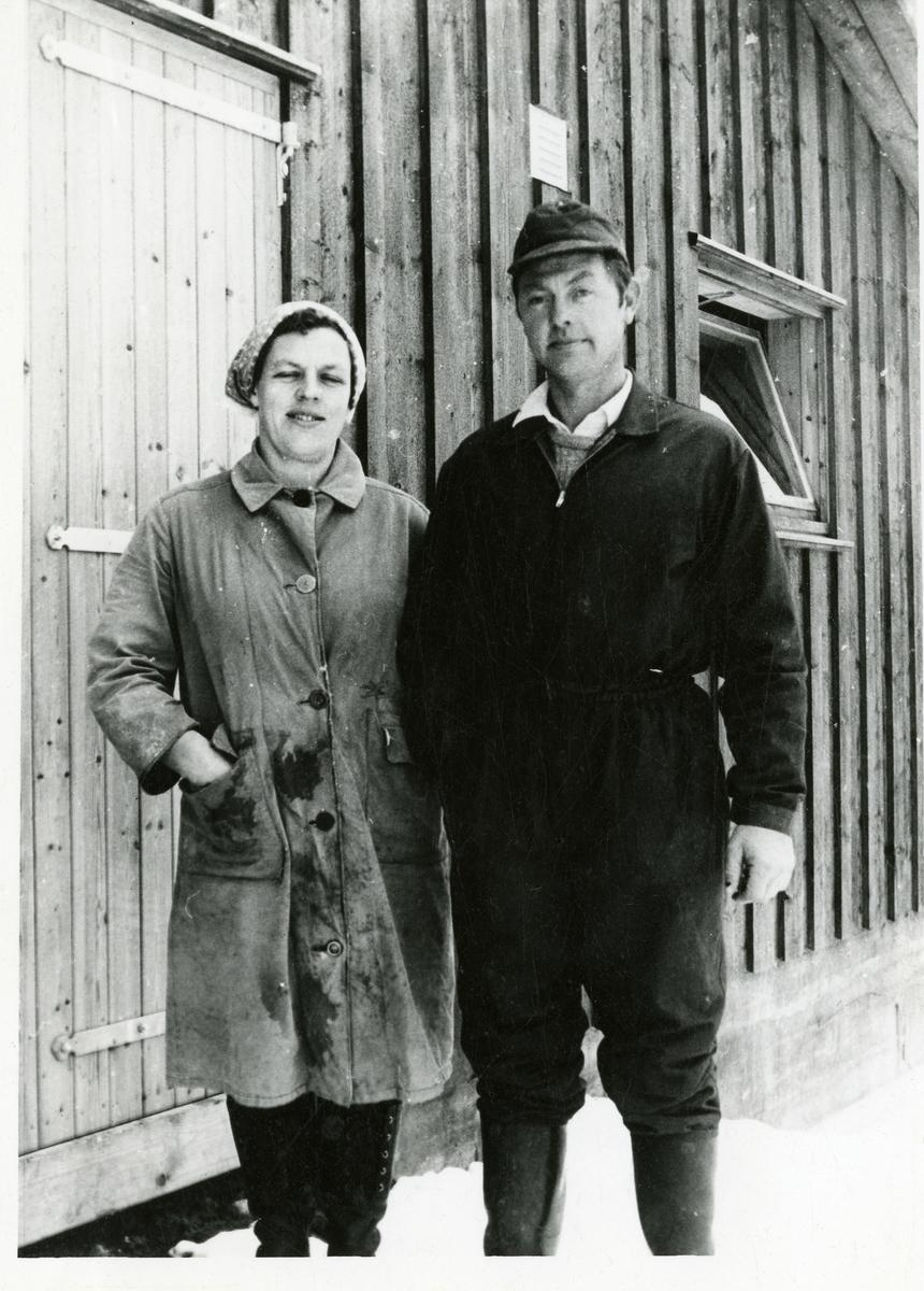 Maria og Martin Bakke står utenfor fjøset på garden Øverby, Hedalen, Sør-Aurdal.