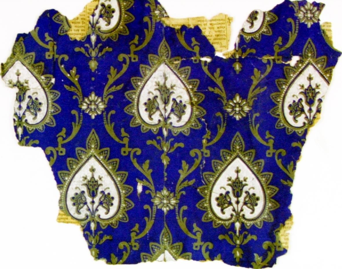 Medaljong i form av hjärta i diagonalupprepning. Tryck i vitt och ultramarin på ett ljusgrått genomfärgat papper.