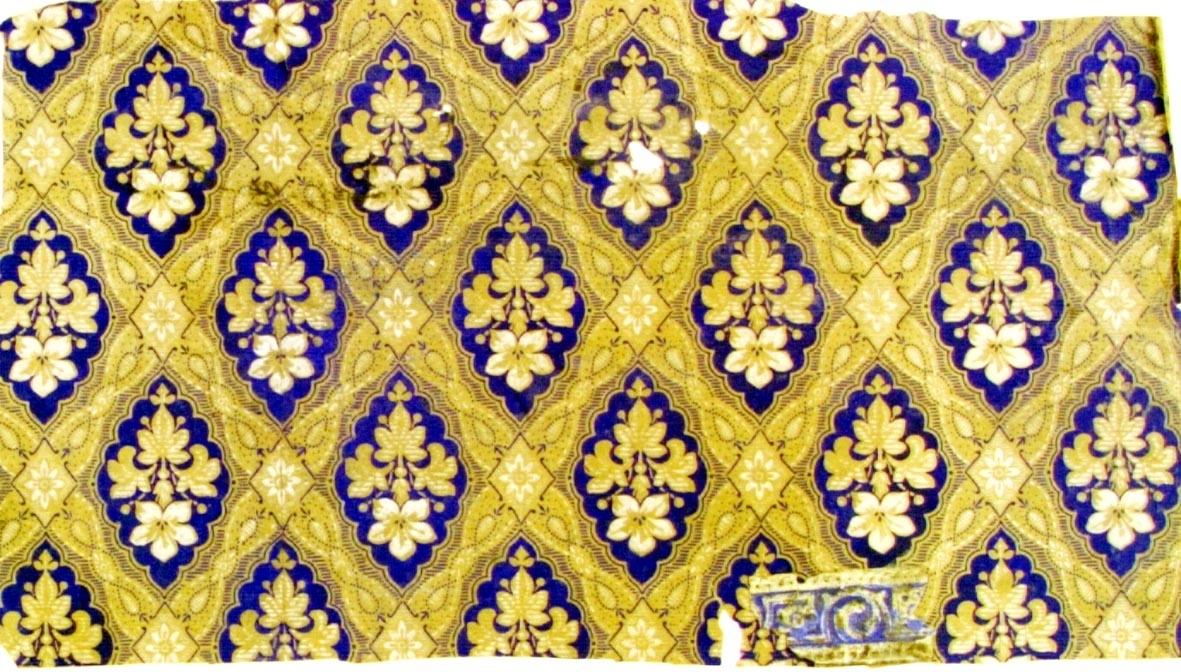 Snedrutmönster där varje kryss respektive ruta är dekorerad med liten blomma respektive blomma med tre blad. Tryck i vitt och ultramarin på ett ofärgat papper