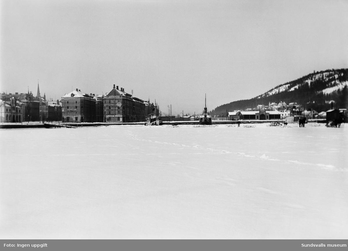 Vy med hamnen vintertid, magasinbyggnaderna, Infrusna båtar.