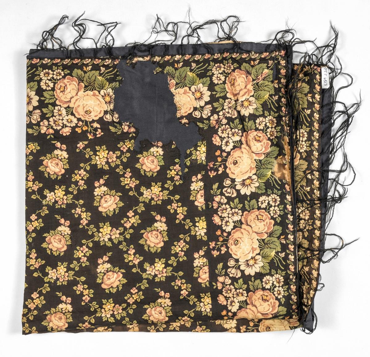 Tørkle i trykt bomulltøy, kypertvove. Brunsvart i botn med rosemønster i beige, lys brunt, grønt og gult. Påsette frynser i ull. Tørkledet er fóra med svart bomull, og stoppa til tørkledet der det er hol.
