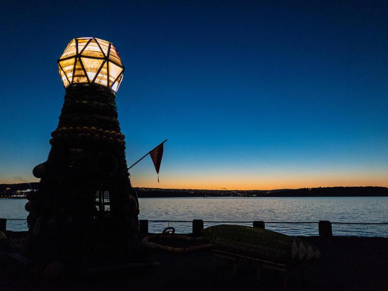 Kveldsstemning ved Fyrtårnet ved Norsk Maritimt Museum, laget av søppel fra havet. Mørkeblå himmel, antydning til solnedgang. (Foto/Photo)