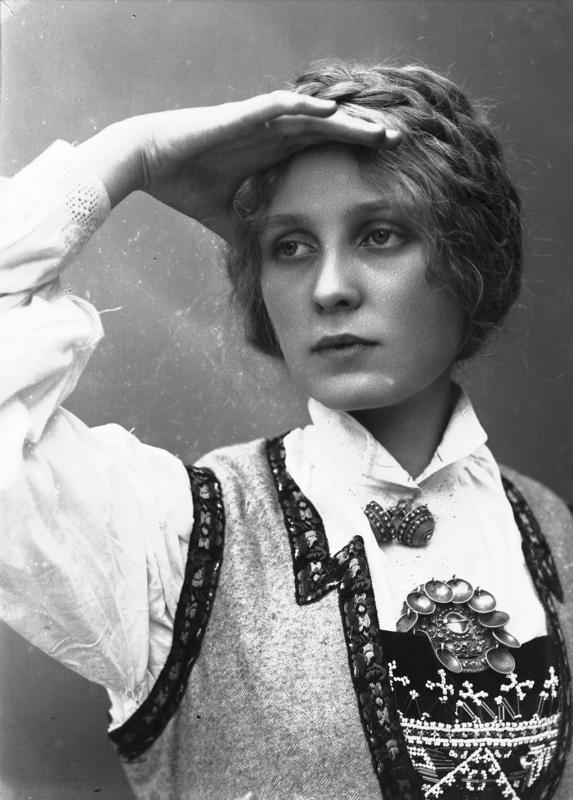 Studioportrett av kvinne i drakt og oppsatt hår som speider. 1908.