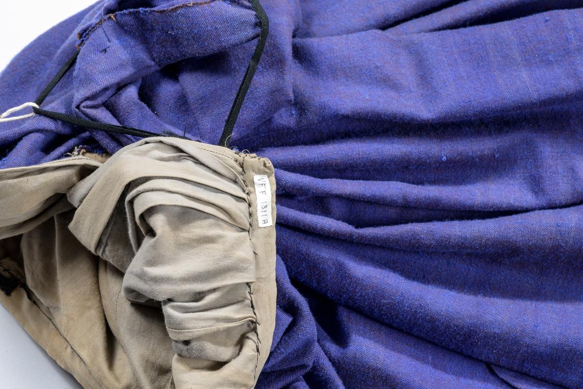 Kjole, to-delt, Stakk, (B) i lilla heimevove tøy. Motfold midt framme, foldekappe nederst og kø bak i det lilla ulltøyet, ellers er (understakken) i bomull. Utanpå ein overstakk som er brodert med kjedesting med svart ullgarn framme og på kanten nede. Kjoleliv (A) i same tøyet. Opning midt framme med 14 knappar (forskjellige) og handsydde knappehol. På kragen, på kvar side av opninga, og nede på ermet er det brodert kjedesting. To snitt på kvar side framme, og to svinga saumar på kvar side av midtsaumen bak. Bakovertrekte skuldersaumar. Todelt erme.