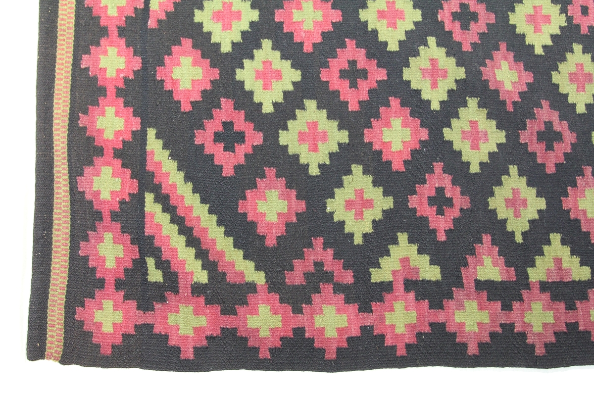 Åkle med renning av lin, islett av ull. Sort bunn, mønster i kirsebærrødt og gulgrønt. Rombeformet midtrute sammensatt av åtte konsentriske felter - regnet innenfra: grønt, rødt, sort, grønt, rødt, sort, grønt, rødt. Like innenfor borden er det øverst og nederst en halvrombe utformet etter lignende skjema, og i hvert hjørne er en kvart-rombe. Omkring midtromben er det seks ganske små kors, to grønne og fire røde, samt to små røde ruter med sort midte. Forøvrig er det ut over flaten jevnt fordelt små ruter, røde med sort eller grønn midte og grønne med røde ruter med grønt midtparti. Perlebord aller ytterst både øverst og nederst. Består av to stykker som er sydd sammen på midten.