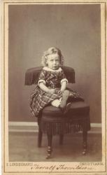atelierfotografi av ein liten gut med ljose krøllar kledd i