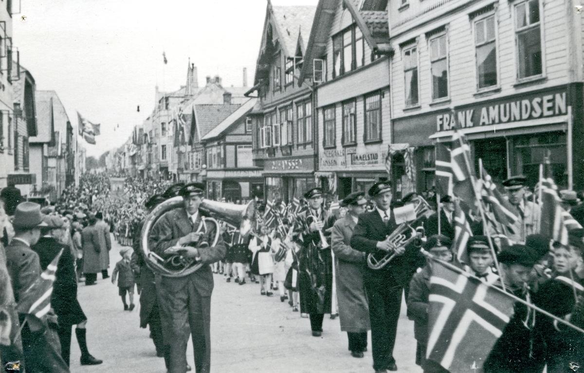 17. mai tog i Haraldsgt. Musikk-korps. Barn med flagg. Hull etter stifter i hjørnene.