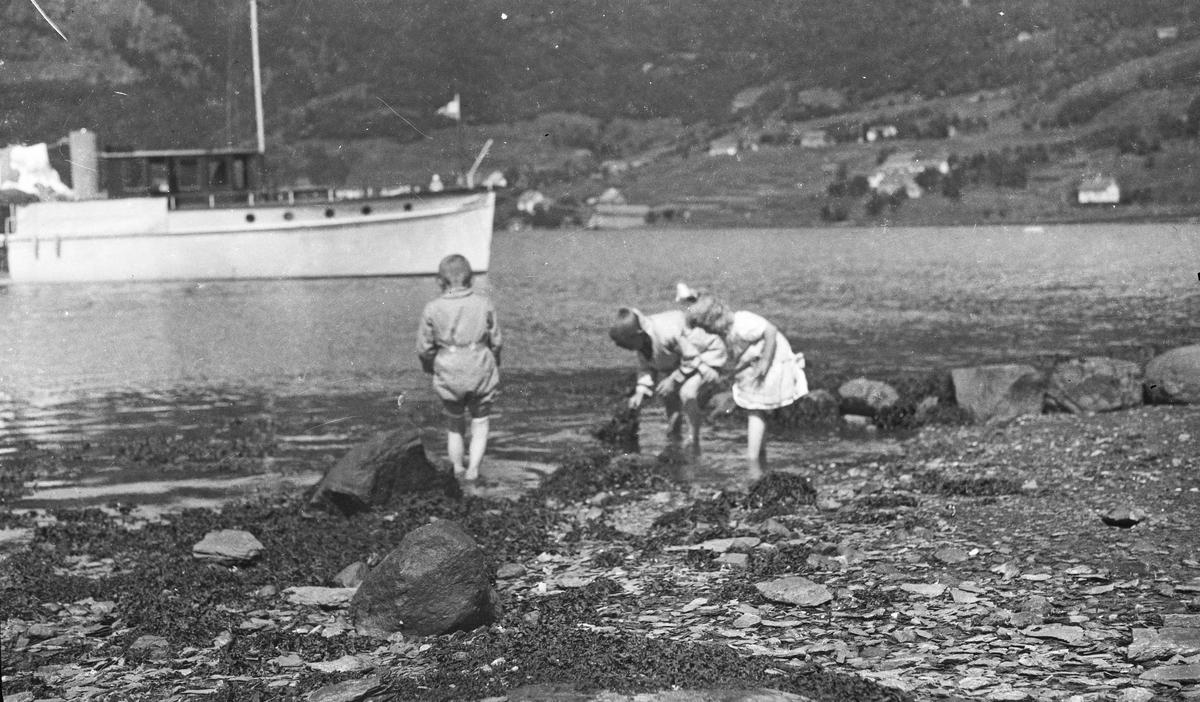 Sommer. To unge gutter og ei ung pike leker på stranden. Motorbåt på sjøen. Fjell i bakgrunnen. Hverdagsfoto.