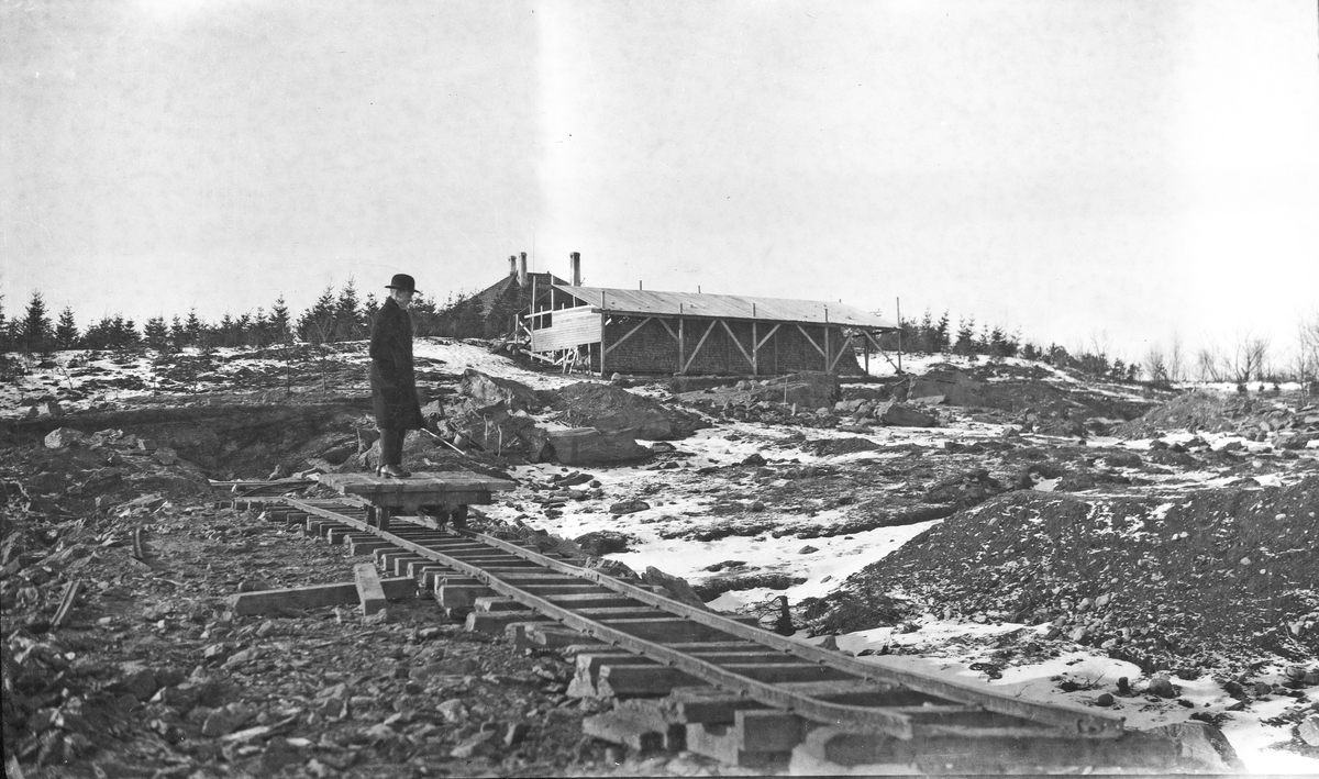 Utgraving. Byggeplass. En mann i hatt og frakk står og ser på arbeidet som er gjort på eiendommen. Hus under oppføring i bakgrunnen. Hverdagsfoto.