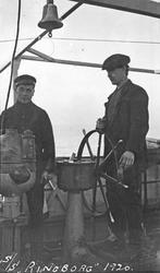 """To av mannskapet på """"S/S Ringborg"""", den ene står til rors. H"""