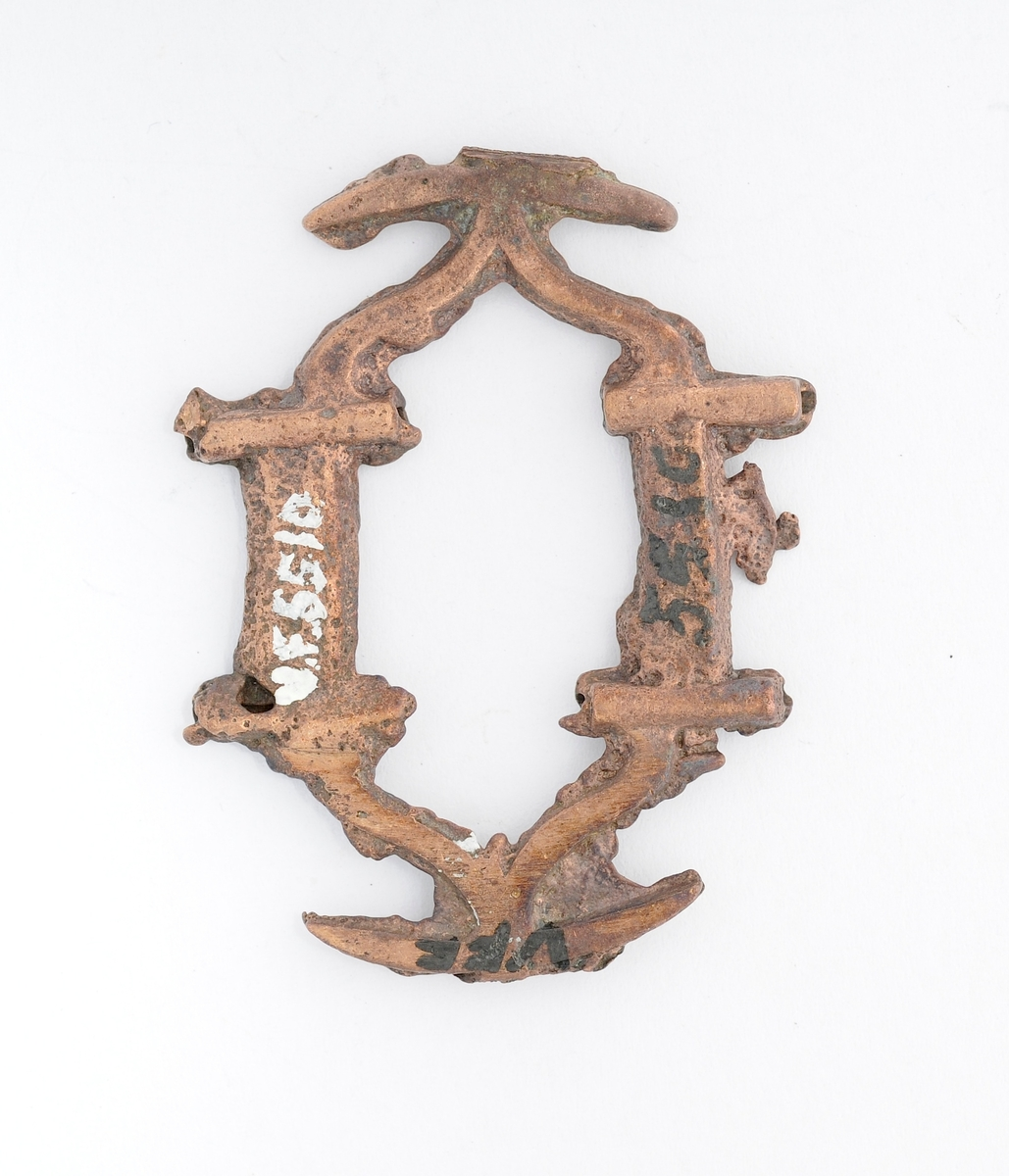 Spenne i messing (bronse?), støypt. Rektanguler form som endar i spissar i endane. To hol på kvar side av langsida for feste av nål. Nål og tein manglar.
