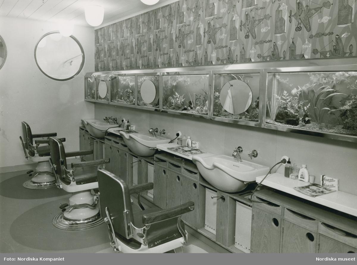 Interiör, frisersalong. Nordiska Kompaniet. Tre stolar framför sköljkar. På väggen ovanför inbyggda akvarier samt en målning eller tapet med mönster av flygplan och byggnader. På en bänk ligger olika nummer av serietidningen Musse Pigg,