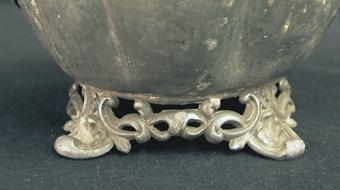 Tekanna, buken av åtta vulster. Knappen på locket, en fruktklase. Ornerade fötter m.m.