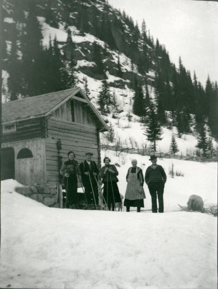 5 personer står foran en tømmerlåve, og 3 av dem har skiutstyr