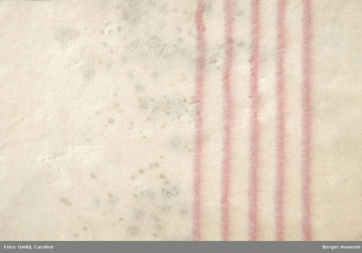 En prøve. Ensfarget, hvitt teppe brutt av bord i fem rosa striper.  Litt skitten, noe møllangrepet.