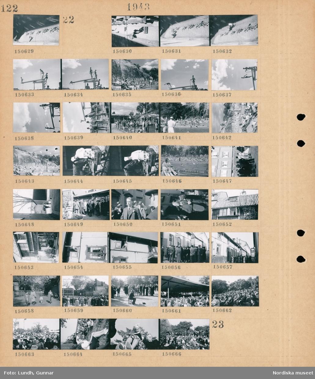 """Motiv: (ingen anteckning) ; Gatuvy med fotgängare och parkerade cyklar.  Motiv: (ingen anteckning) ; Gatuvy med fotgängare och parkerade cyklar, människor solar och badar vid ett utomhusbad, en man i kockmössa matar en häst, en grupp människor står vid en byggnad, en kvinna och en man går på en gata, exteriör av hus, människor står i kö utanför en byggnad med skyltar """"Skomakare"""" """"Skräddari"""", två flickor och två kvinnor går på en  gata, en folksamling, människor står och tittar på en man som sitter på en stol och spelar troligen på en såg, en kvinna och en man sitter på marken, en kvinna läser en bok."""