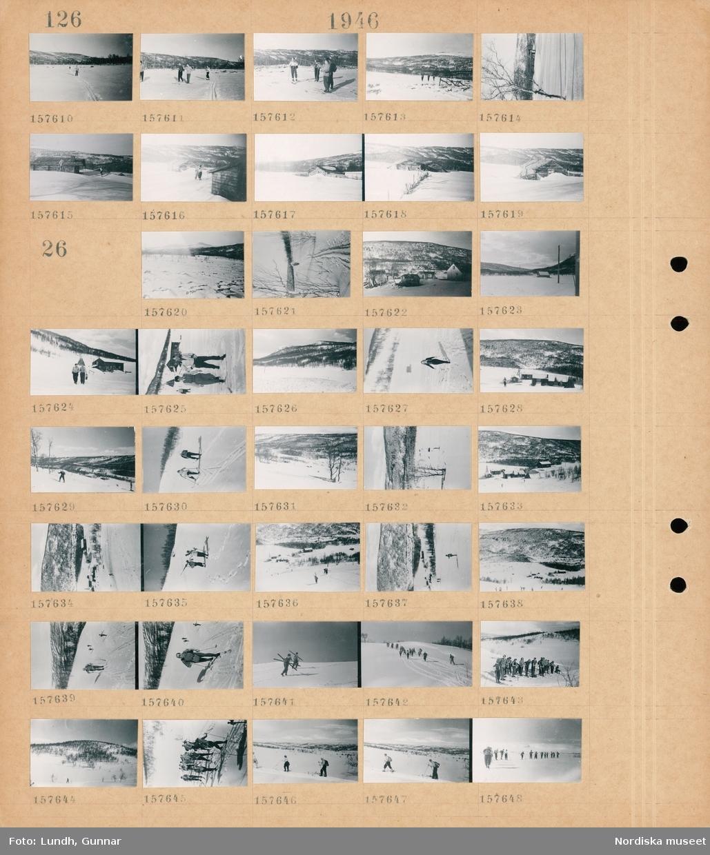 Motiv: (ingen anteckning) ; Snötäckt landskapsvy med fjäll och kvinnor och män som åker skidor, exteriör av hus.  Motiv: (ingen anteckning) ; Snötäckt landskapsvy med fjäll, exteriör av hus, kvinnor och män åker skidor.