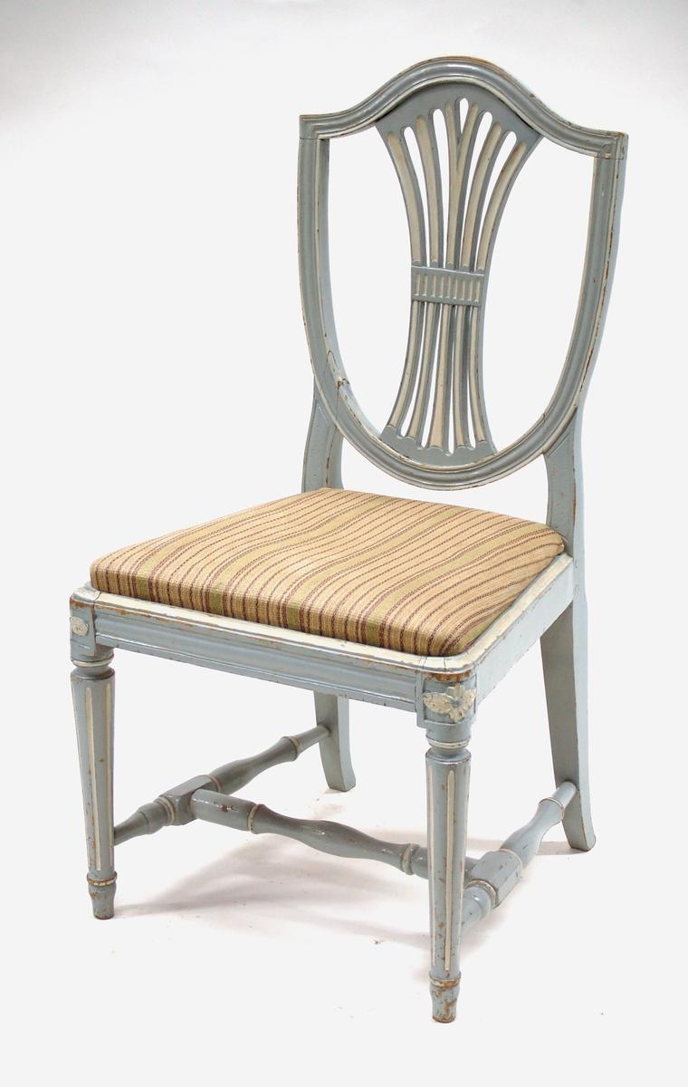 """Katalogkort: Stol, gråblå och vit. Sköldformad, profilerad rygg med ryggbrickan av böjda spjälor. Rak, profilerad sarg. Raka profilsvarvade framben i höjd med sargen en reliefskuren blomma. Fyrsidiga, svagt utåtsvängda bakben. Benkryss. Den vita färgen använd i dekorativt syfte. Stoppad sits klädd med beige-, lila- och grönrandigt tyg. Gustaviansk (Hepplewhite) Signerad """"IHS"""" (Johan Hammarström, stolmakare i Stockholm 1770-ca1790)"""