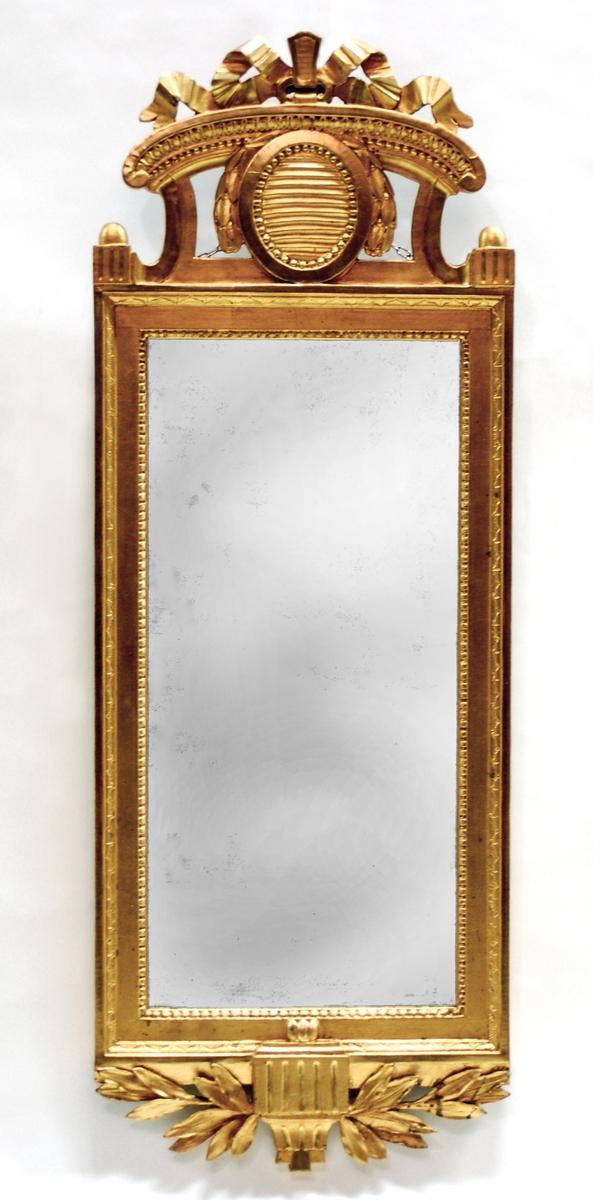 Kat.kort: Spegel, förgylld. Långsträckt rektangulär ram med nyklassicistiska bårder. Överstycke med lagerblad.