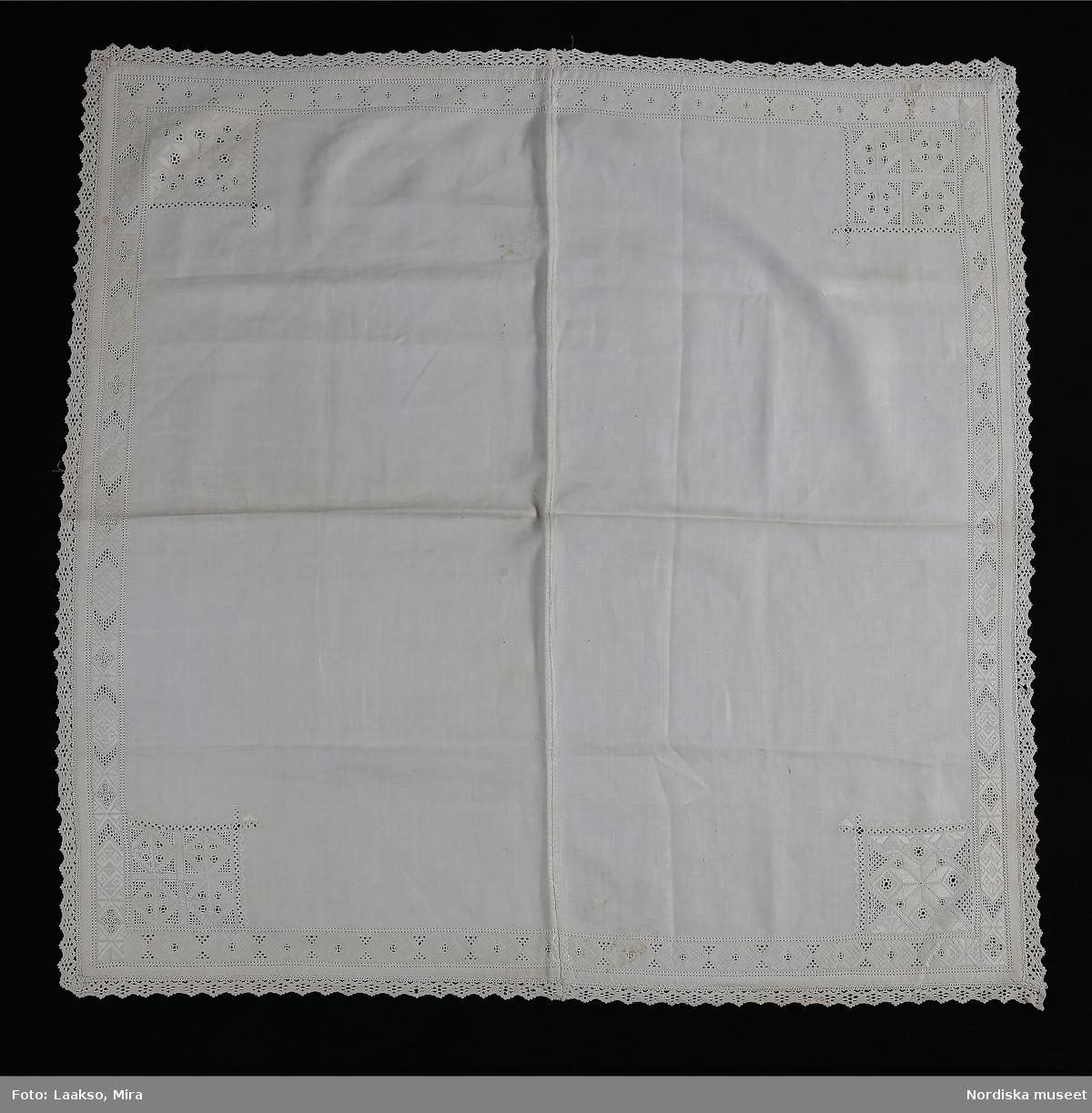 Kvadratiskt kläde av handvävd vit linnelärft, hopsytt av 2 delar. 1 cm bred fåll sydd med 2 rader enkel utdragssöm s.k. tandrad, 2,5 cm bred kantbård broderad i rätlinjig plattsöm och utskuren söm, i varje hörn ett kvadratiskt broderi 9,5 x 9,5 cm med samma typ av broderi, olika mönster i varje hörn. Klädet kantat med 1,5 cm bred knypplad uddspets av ålderdomlig flätslagstyp. I vaje hörn på avigsidan en liten tränsad trådhank som har varit fäste för en hängande hörnprydnad, oftast en broderad lapp med spetskant. Anm. Mittsömmen är sekundär, har från början varit ett helt stycke. Denna typ av linnekläde från Värendsområdet hör till samma dräktområde som Skåne och Blekinge där liknande kläden använts till högtidsdräkten som handkläde och vid kyrkbesök som bokkläde kring psalmbokem. Vid stora kalas har det även kunnat användas som förningsduk kring medförda varor.  Vid begravningar har det även kunnat bäras som huvudduk. /Berit Eldvik 2010-06-23