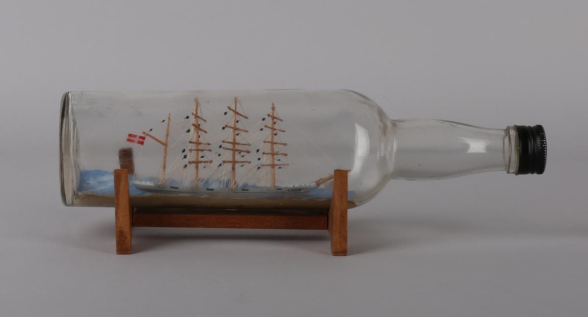 Flaskeskute i rund flaske med modell av bark LUNA i åpen sjø. Med det norske flagg akter.  Står på lite trestativ.