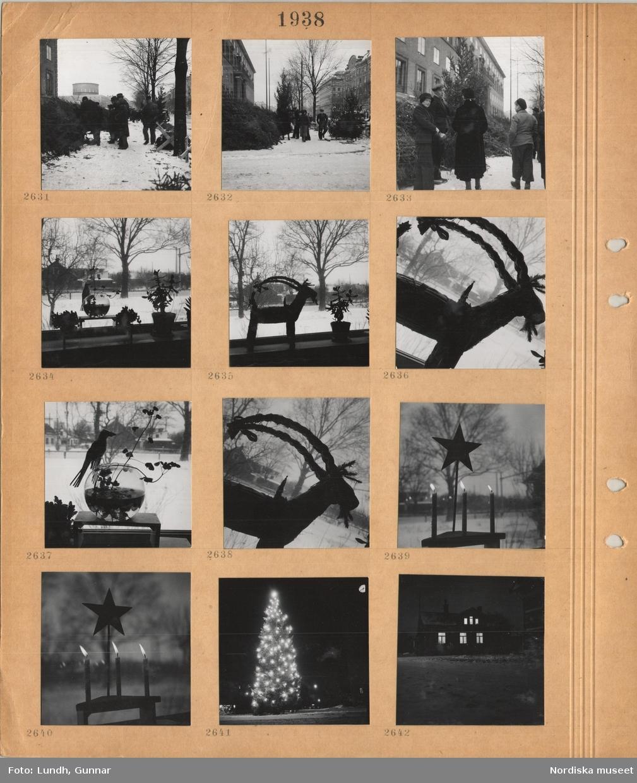 Motiv: Julgransförsäljning, i stadsmiljö, Stadsbiblioteket i bakgrunden,  köpare, fönster med krukväxter, utsikt mot villaområde, halmbock med liten tomte på i fönster, ljusstake med tända ljus, femuddig stjärna, hög julgran utomhus med tänd belysning, husexteriör i mörker, upplysta fönster, snö på marken.