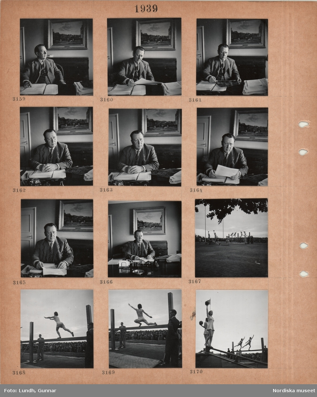 Motiv: En man, Hjalmar Engberg, i kostym med väst, sitter vid ett skrivbord med papper, kvinnliga gymnaster har uppvisnig eller tävlar utomhus, stor publik.