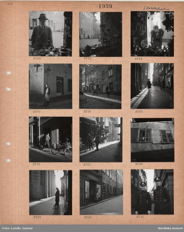 Motiv: Stockholm, en man tittar i ett skyltfönster fullt med saker, en kvinna står i ett gathörn, skyltfönster, barn och en man på en stenlagd gata, äldre hus, butiksskyltar, två kvinnor på en gata, parkerade cykel, en man bär möbler, kvinna tittar ut genom ett fönster, en man står i gränd utanför Storkyrkan, kvinna står vid en port med löpsedlar på dörrarna, två poliser i uniform.