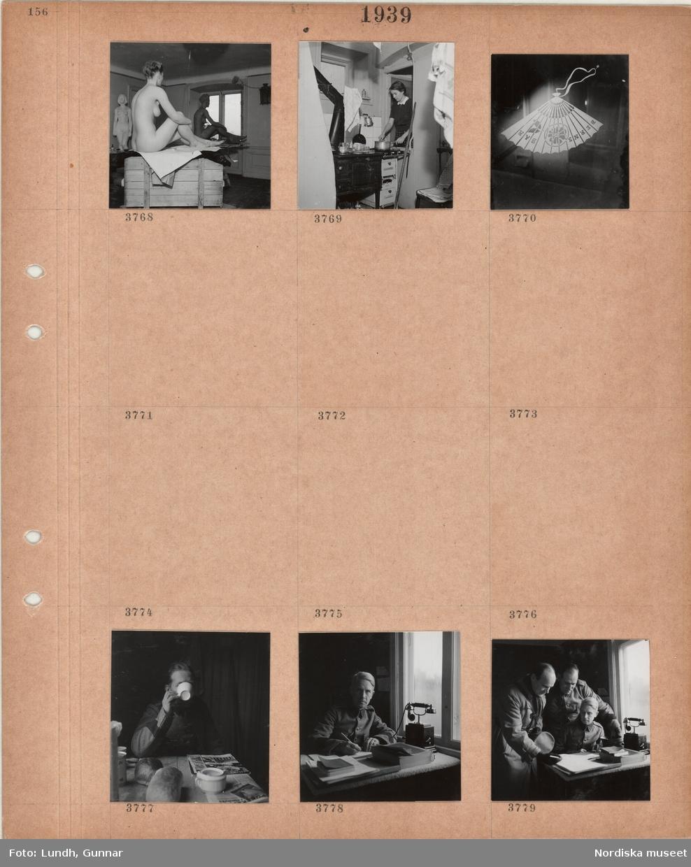 """Motiv: Interiör konstateljé, nakenmodell samt skulpturer, kvinna arbetar i ett enkelt kök, fönster med solfjäder med texten """"BERNS BAR"""", man i uniform vid frukostbord, man i uniform vid skrivbord, telefon, tre män i uniform vid skrivbord."""