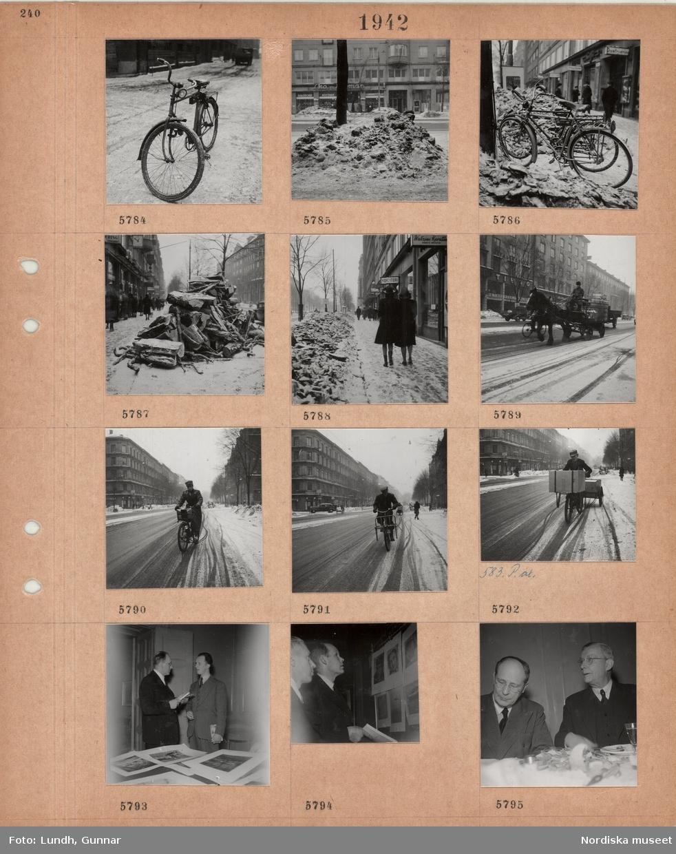 Motiv: Herrcykel parkerad på snöig gata, uppskottade snöhögar på trottoarer, parkerade cyklar, hög med virke på trottoar, butiksskyltar, gående, hästdragen kärra med mjölkflaskor, kusk, cyklande man i uniform, paketcyklar, två män i kostym vid ett bord med utlagda konstverk, två män tittar på upphängda konstverk, två män i kostym sitter vid ett matbord.