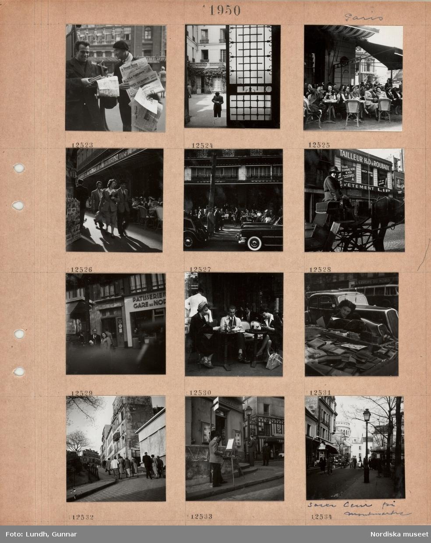 Motiv: Paris, en man med karta i handen står bredvid en dagstidningsförsäljare med basker, inblick mot innergård, smidesgrind med glas, uteservering på trottoar, gäster sitter vid små bord, markiser, fotgängare på smal gata mellan uteservering och tidningsstånd, parkerade bilar framför uteservering, hästdroska med kusk framför klädaffär, gäster på uteservering, servitör, kvinna läser en tidning framför stånd med plånböcker, trafik i bakgrunden, fotgängare på väg uppför en brant gata, flerbostadshus, en konstnär står på trottoar och målar vid staffli, gata med fotgängare, gatlykta, i bakgrunden kyrkan Sacre Coeur med kupoler, Montmartre.
