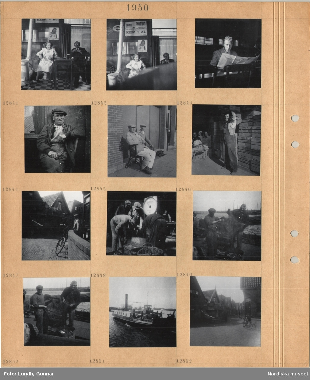 Motiv: En kvinna och en man sitter vid ett kafébord, värmekamin, en man sitter och läser tidningen, porträttbild av sittande man i arbetskläder, två äldre män sitter i stolar på trottoar, hund ligger bredvid, man i arbetskläder tar en lådapå axeln, stenlagd gata, cykel lutad mot mur, stor varuvåg, vägning av fisk, två fiskare skakar ut fångst ur nät vid kaj, bilfärja, gata med hus med gavlarna mot gatan.