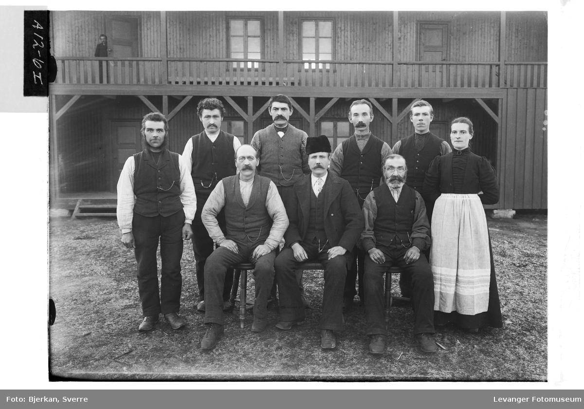 Gruppe mennesker på et gårdstun, drengstuggu i bakgrunnen. Mann på svalgangen er blitt med i bildet.