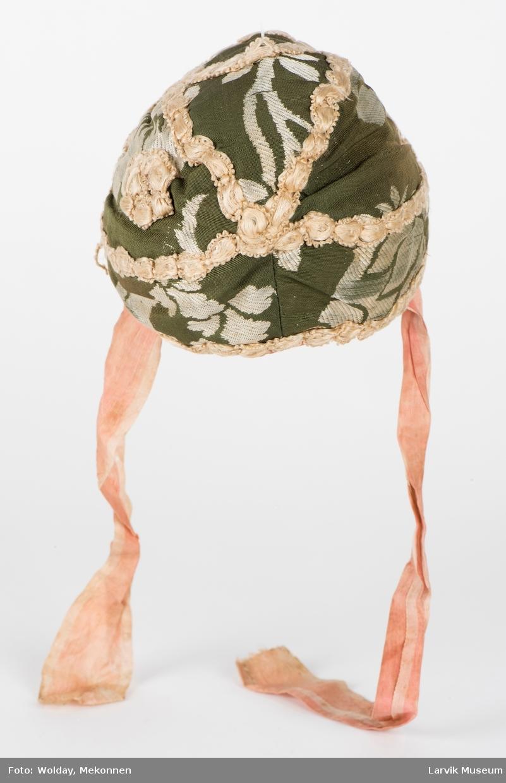 5 kileformede deler, blonder rundt kant, 2 hakebånd. Grønn bunn, mønster i hvit jacquard, påsydde gulhvite blonder; alt i silke. Fôret er av hvit bomull med rødt og svart påtrykt mønster. Hakebånd av rosa silke, liksom kanten rundt hele luen.