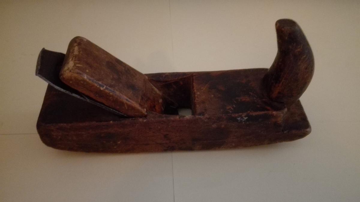 Velbrukt rundhøvel høvel i tre, med trekile og høveljarn. Handtak framme. Sålen er runda i lengderetninga.  Høvelen kan ha vore brukt både som snekkarreiskap ved husbygging og til båtbygging.
