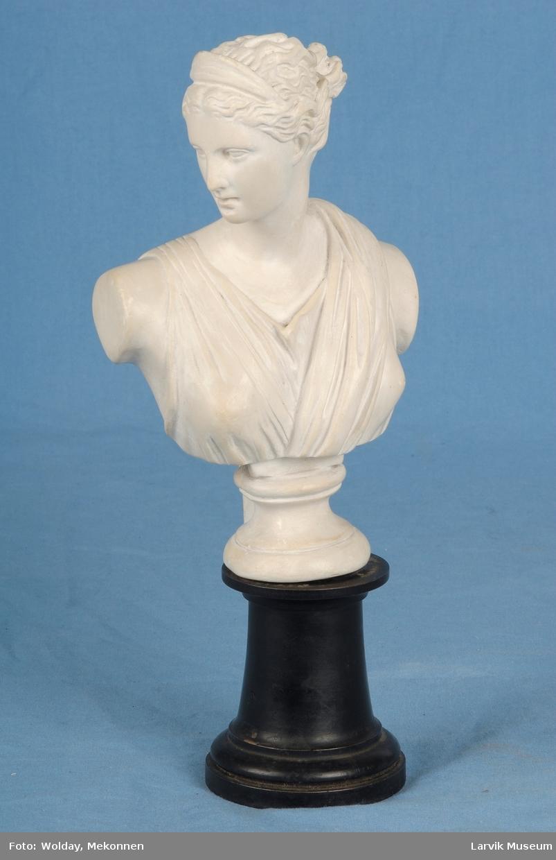 Byste av den greske gudinnen Artemis. Bysten har et hull under som tres nedpå en plugg på fotens øvre flate.