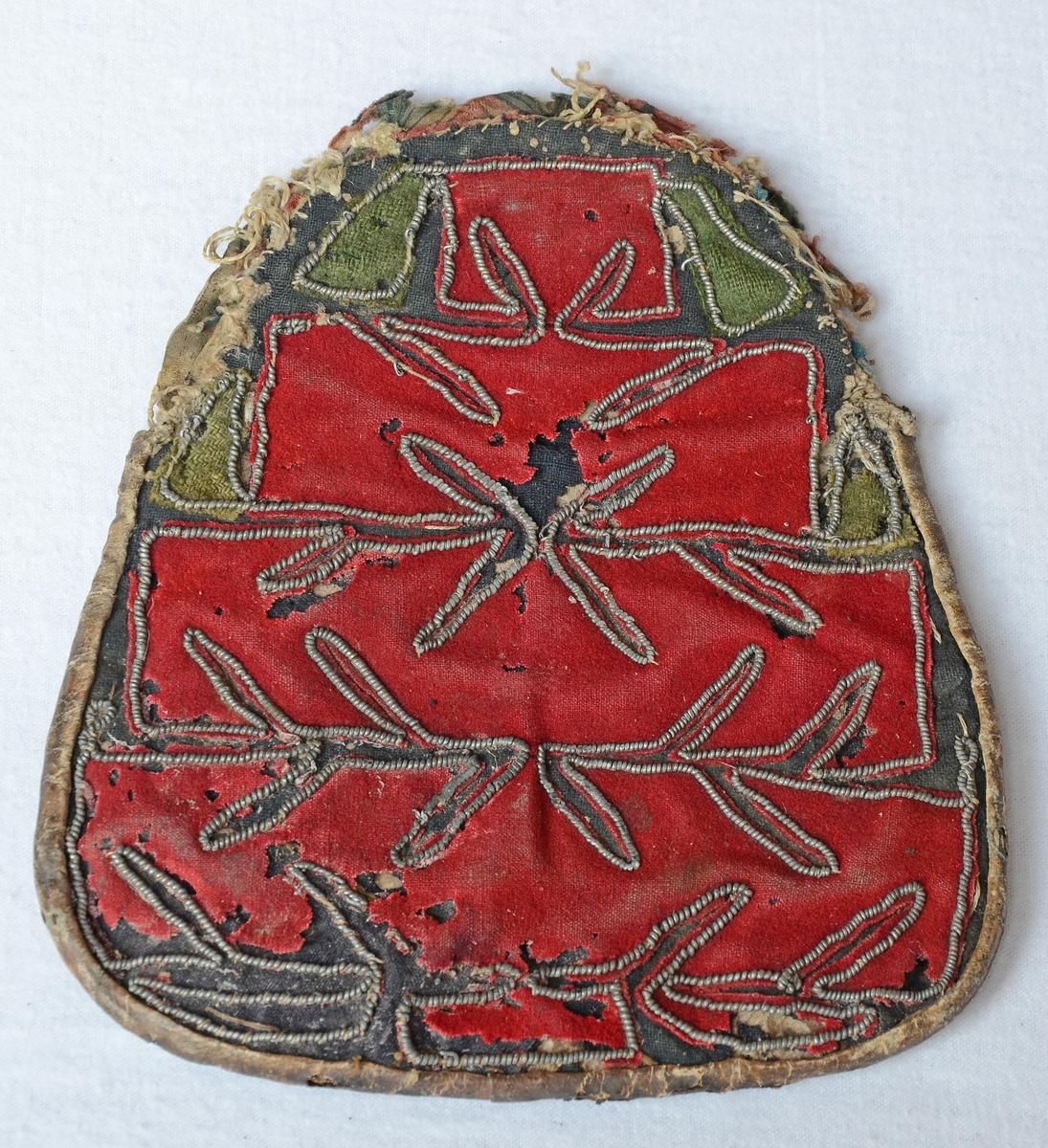 Kjolväska med applikationer i rött och grönt,  kantat med tenntråd, på svart botten. Baksida av skinn. Fodrad med tryckt bomullskattun och grovt linne.