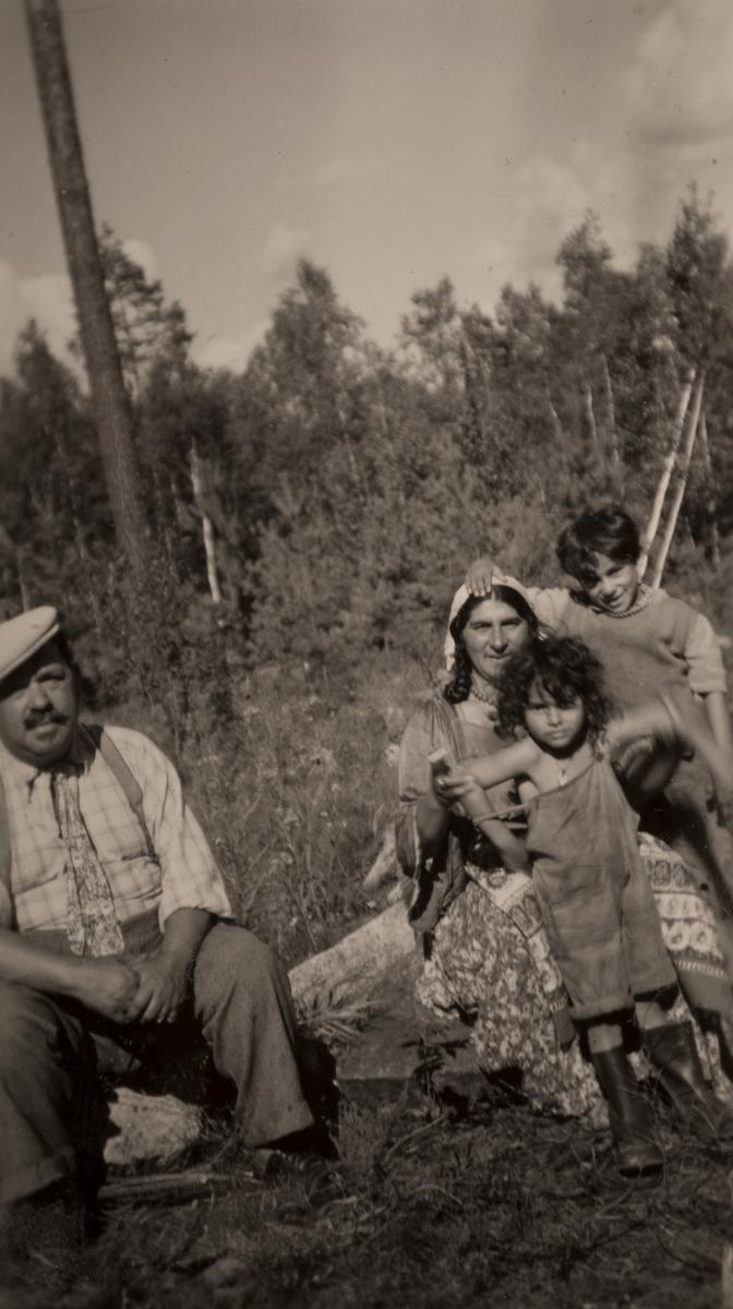 En grupp romer har slagit sig ned för att bli avfotograferade. Två barn klänger på en kvinna och en man sitter bredvid. Bilden är tagen i Hofors 1950.