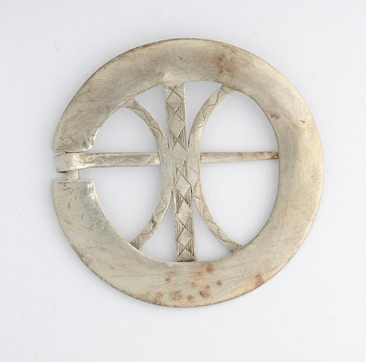 Sølje, bringering i sølv (utan stempel). Rund, (støypt ?) med ei nål (tann). Pålodda midtstolpar med gravert mønster. Glatt på baksida.