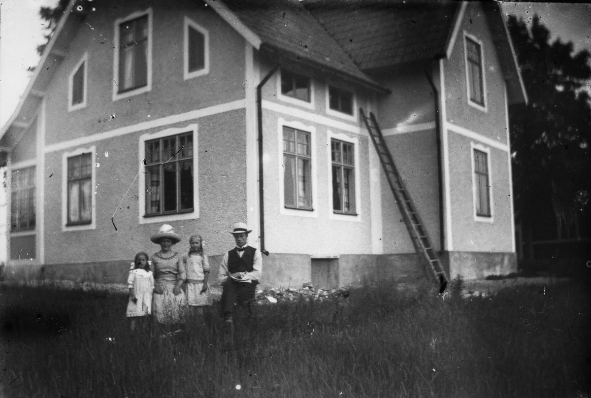 Två vuxna och två barn framför ett bostadshus.